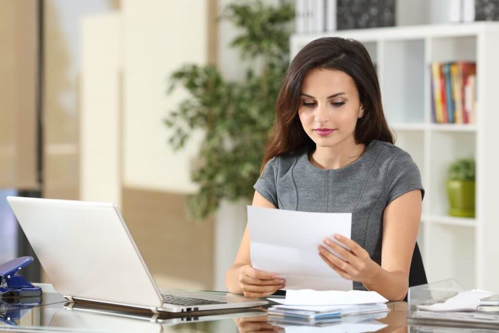 woman reading mail at desk