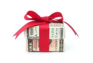 gift box wrapped with dollar bills and red bow