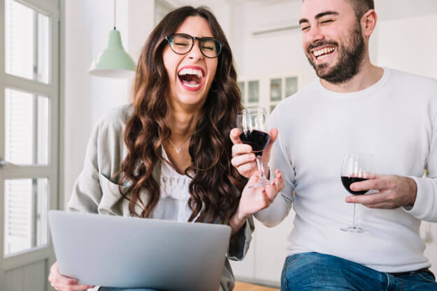 two people laughing and drinking wine