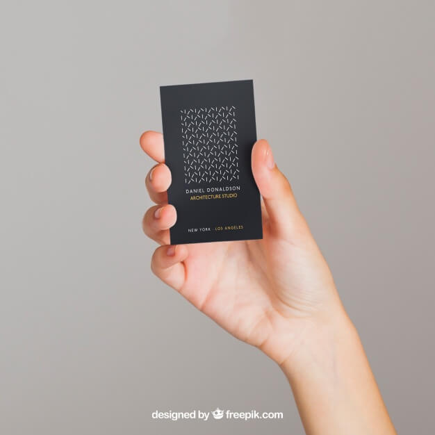 hand holding black business card with simple white and yellow design