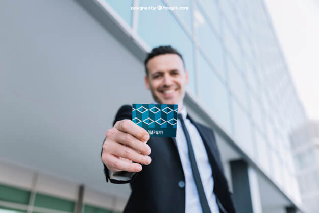 businessman smiling and holding out business card