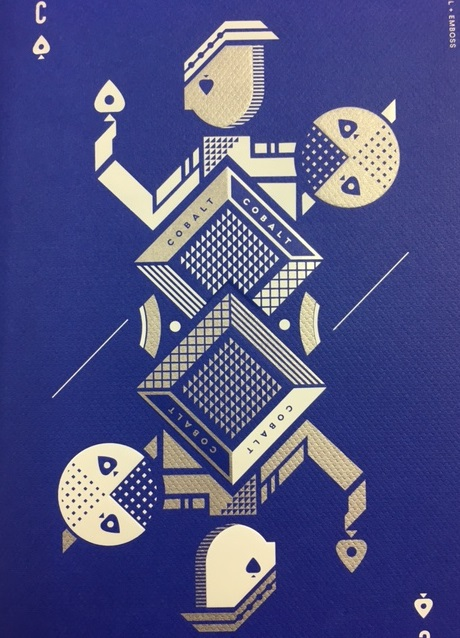 artistic rendering of a playing card in white and silver ink printed on a blue paper stock