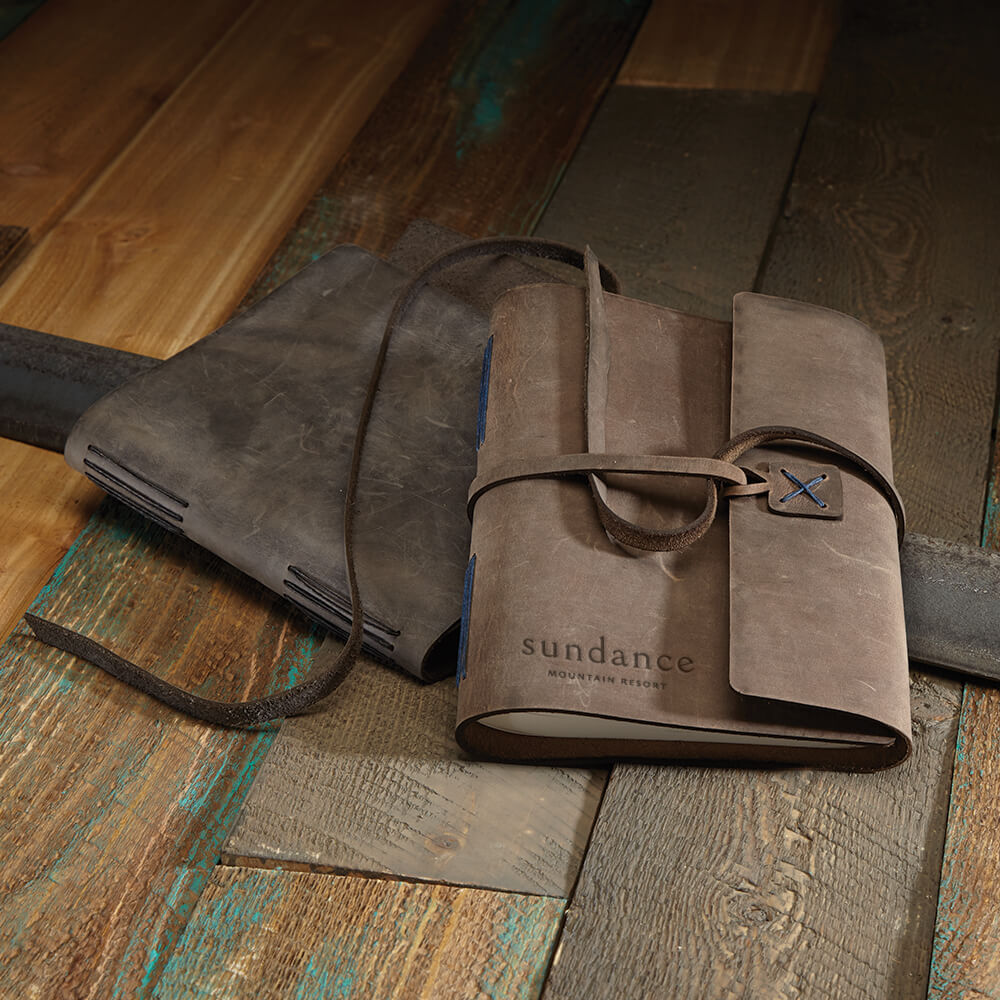 brown leather journal with tie laying on wooden boards