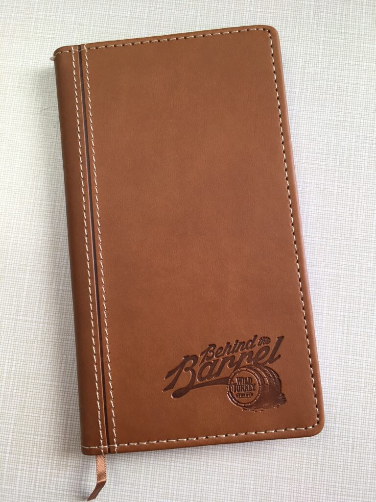 brown leather journal with white stitching and embossed artwork