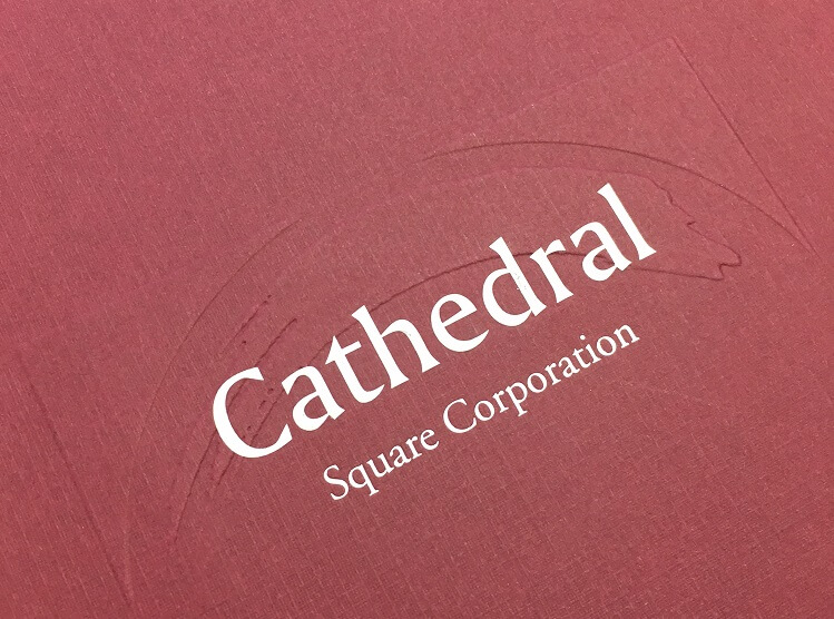 Red folder decorated with embossing reading Cathedral Square Corporation in white