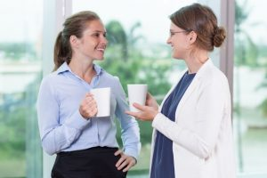two smiling women drinking tea and speaking in office