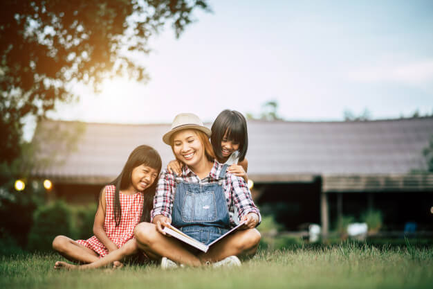 woman reading story to young daughters in garden
