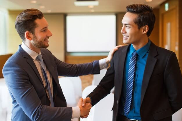 two men shaking hands and smiling