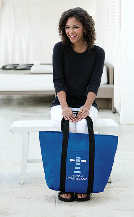 Young woman smiling and holding blue branded tote bag