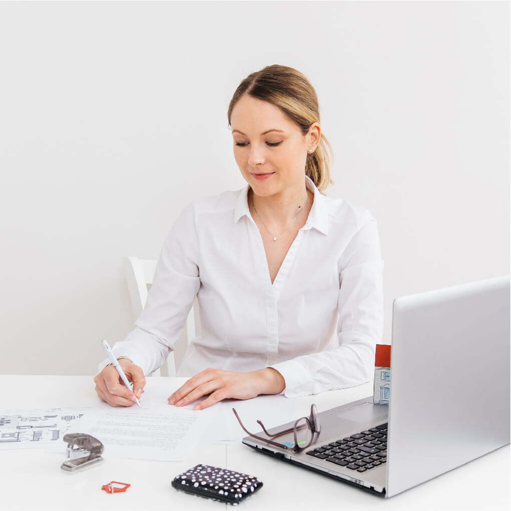 Young woman writing fundraising appeal seated at desk