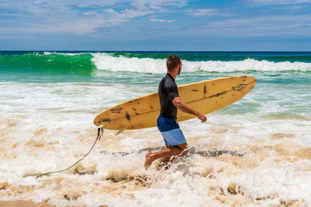 Man with surfboard on beach Australia