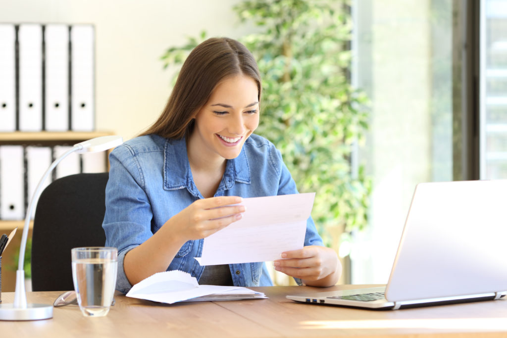 Young smiling businesswoman reading a direct mail letter at desk