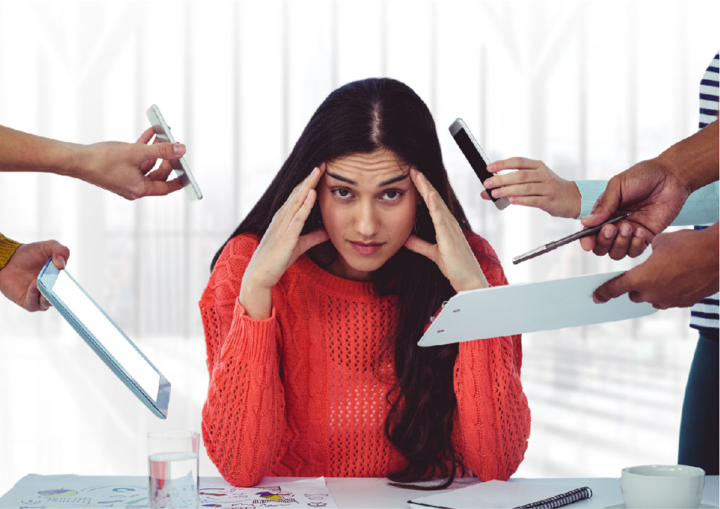 Stressed woman at desk surrounded by distractions
