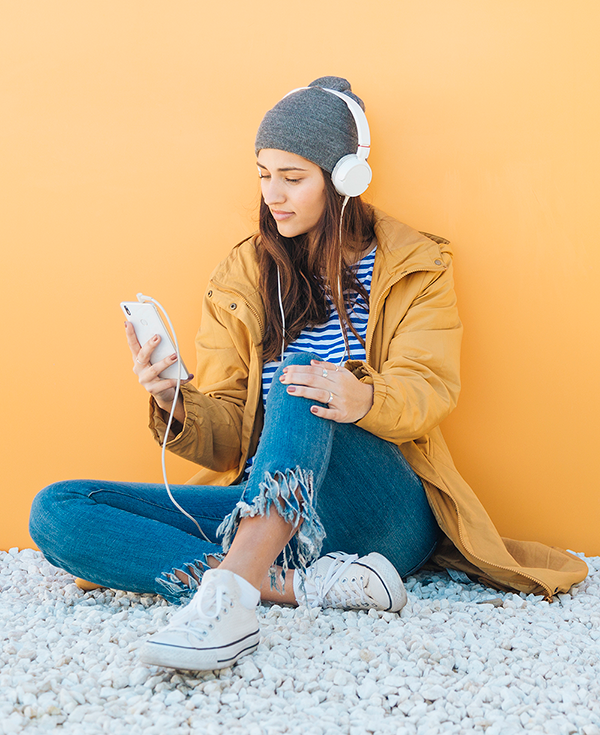 Young woman listening to music on cell phone