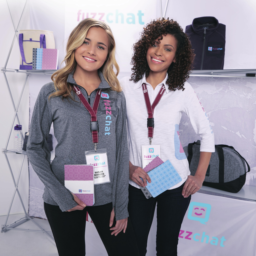 Two women posing with promotional products at trade show