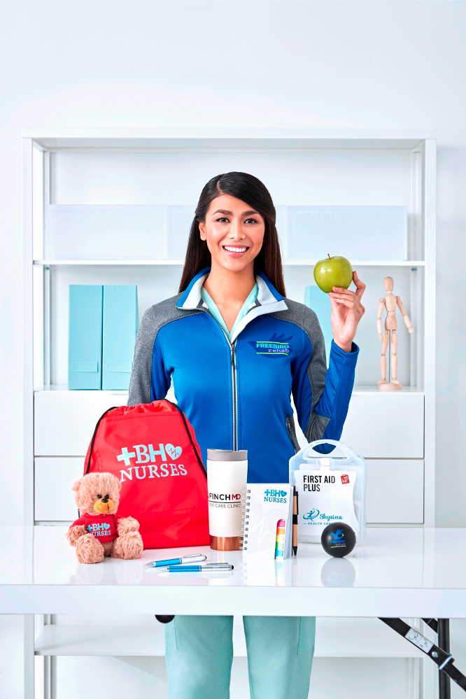 woman holding an apple behind table of branded promotional products