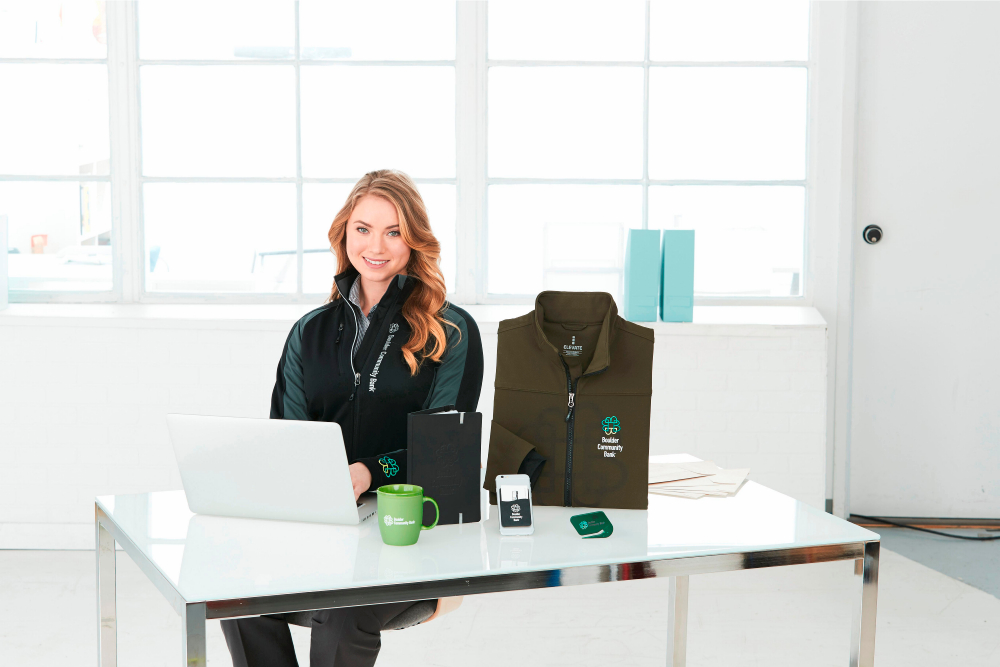 Woman working at desk surrounded by promotional products
